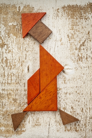 abstract figure of a walking woman built from seven tangram wooden pieces, a traditional Chinese puzzle game; rough white painted barn wood background photo