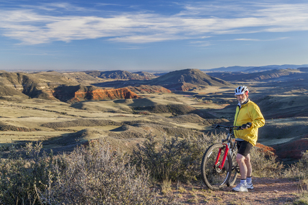 red mountain open space: senior male mountain biking in rugged terrain with cliffs and canyon of Red Mountain Open Space in northern Colorado near Fort Collins Stock Photo