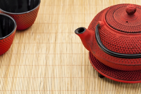 hobnail: Japanese tetsubin and tea cups on a bamboo mat - a traditional cast iron red hobnail design with black enamel inside Stock Photo