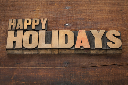 happy holidays text: happy holidays  - text in vintage letterpress wood type blocks on a grunge wooden background Stock Photo