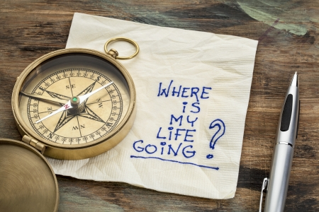 searching for: where is my life going - an essential question or searching for purpose  - a napkin doodle with a brass compass Stock Photo