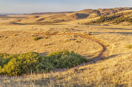 soapstone: sunrise illuminates a trail through rolling prairie at foothills of Rocky Mountains in Colorado - Soapstone Open Space near Fort Collins