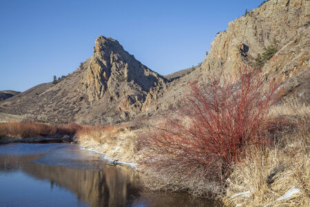 eagle nest rock: Eagle Nest Rock and partially frozen North Fork of Cache la Poudre River in northern Colorado at Livermore near Fort Collins, early spring Stock Photo