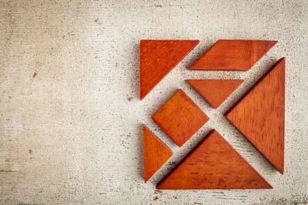 tangram: seven tangram wooden pieces, a traditional Chinese puzzle game, rough white painted barn wood background Stock Photo