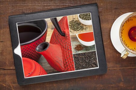 tetsubin: reviewing pictures of tea on a digital tablet, a grunge wood background with a cup of hot tea