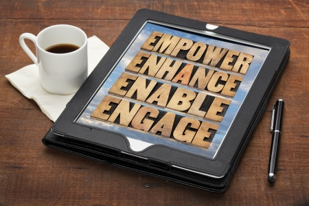 empower, enhance, enable and engage - motivational business concept - a collage of words in letterpress wood type on a digital tablet Stock Photo
