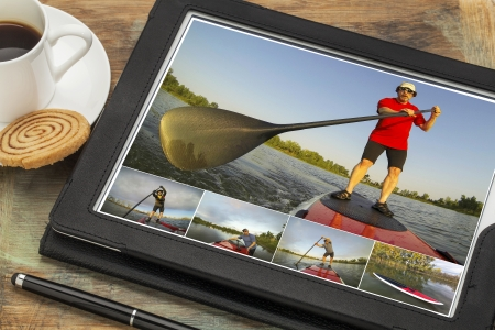 reviewing pictures of stand up paddling featuring a senior male on a digital tablet computer in black leather case with  coffee cup and cookie, the same model on all pictures Stock Photo - 23172272
