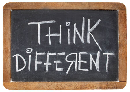 unorthodox: think different - motivational phrase - white chalk handwriting on a vintage slate blackboard