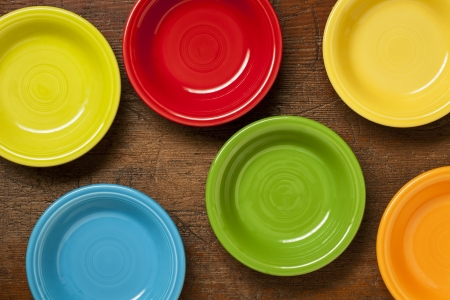 table top: colorful ceramic bowls on a grunge weathered wood table - top view