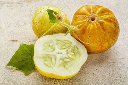 lemon (or apple) cucumbers with cross section and leaf on rough white painted wood surface Stock Photo - 23172286