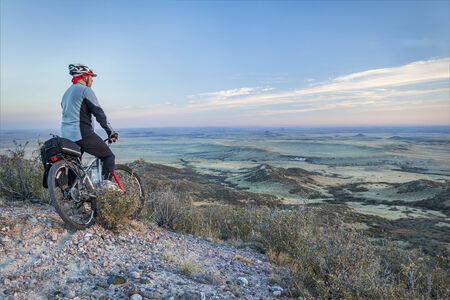 rocky mountains colorado: senior male on a mountain bike contemplating a view of rolling prairie at dusk, Soapstone Prairie Natural Area near Fort Collins, Colorado Stock Photo