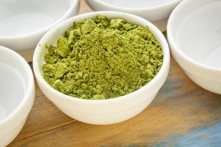 oleifera: moringa leaf powder in a small bowl among empty white bowls Stock Photo