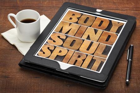mind body soul: mente, corpo, anima e spirito - concetto di benessere - un collage di parole in tipografica tipo di legno su una tavoletta digitale con tazza di caff� Archivio Fotografico