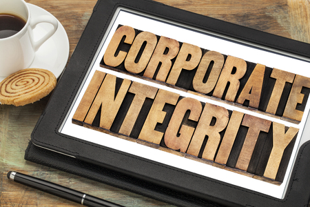 corporate integrity - business ethics concept - text in letterpress wood type on digital tablet computer with stylus pen, coffee cup and cookie photo