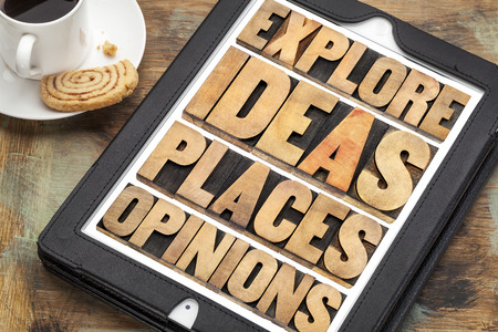 opinions: explore ideas, places and opinions - motivational words in vintage wood type on a digital tablet with a cup of coffee and cookie