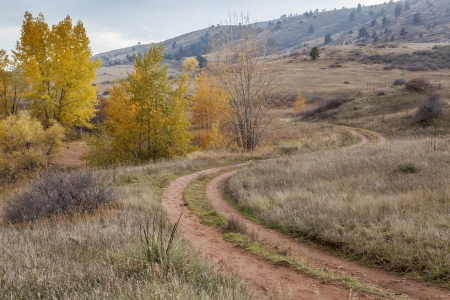 nostalgic autumn scenery - dirt road meandering through Colorado foothills with last foliage color near Fort Collins photo