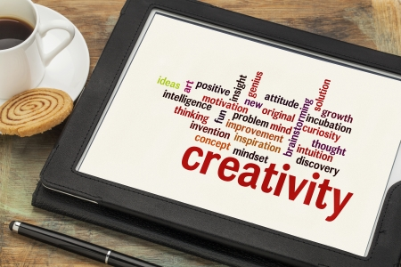 creativity: cloud of words or tags related to creativity on a  digital tablet with a cup of coffee