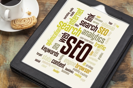 seo: cloud of words or tags related to SEO (search engine optimization) on a  digital tablet with a cup of coffee
