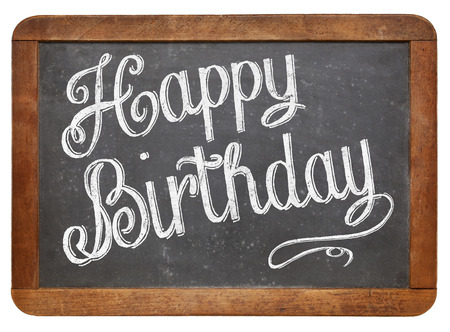 Happy Birthday  - white chalk text  on a vintage slate blackboard isolated on white photo