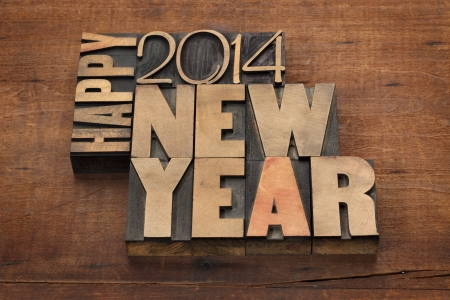 Happy New Year 2014 greetings - text in vintage letterpress wood type blocks on a grunge wooden  photo