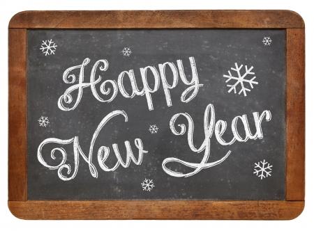 Happy New Year - white chalk text  on a vintage slate blackboard