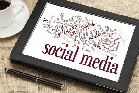 コーヒーのカップを持つデジタル タブレットにソーシャル メディアの単語の雲 写真素材