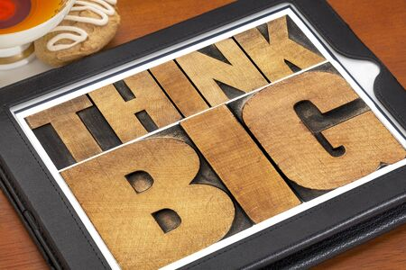 think big motivational phrase in letterpress wood type on a digital tablet with a cup of tea photo