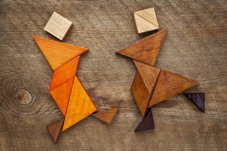 pareja bailando: Una pareja de bailarines o artistas marciales - figuras abstractas construidas a partir de piezas de madera tangram, un juego de puzzle tradicional china