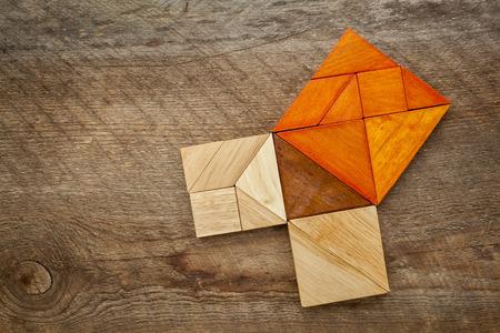 teorema: El teorema de Pit�goras ilustrado con piezas de madera de tangram, un rompecabezas chino cl�sico, contra la madera del granero Foto de archivo