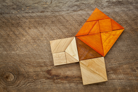 theorem: Pythagorean theorem illustrated with wooden pieces of tangram, a classic Chinese puzzle, against barn wood