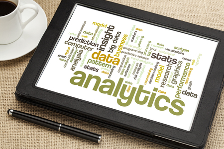 cloud of words or tags related to analytics and data analysis on a  digital tablet with a cup of tea Stock Photo