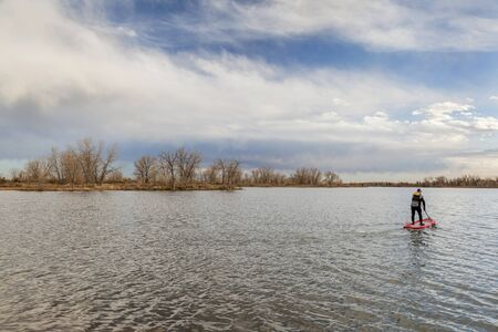 a calm lake in late fall scenery with a lonely male stand up paddler Stock Photo - 23913587