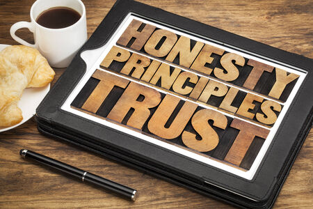 morale: honesty, principles and trust words in vintage letterpress wood type on a touchscreen of digital tablet with a cup of coffee Stock Photo