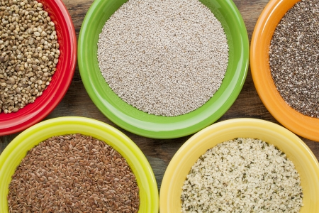 white and black chia, flax and hemp seeds in colorful ceramic bowls Stock Photo