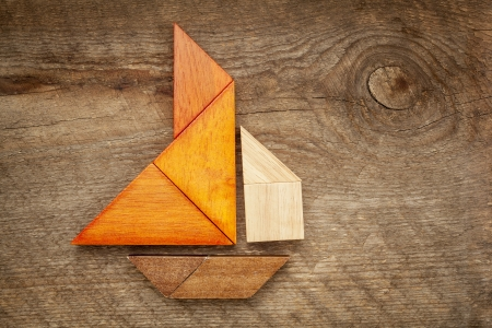 abstract picture of a sailing boat built from seven tangram wooden pieces over a rustic  barn wood, artwork created by the photographer photo