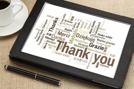 merci: merci en diff�rentes langues - nuage de mots sur une tablette num�rique Banque d'images