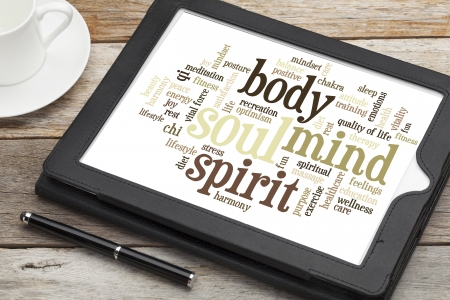 mind body soul: mind, body, spirit and soul - word cloud on a  digital tablet Stock Photo