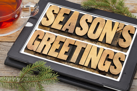 season's greetings typography - text in letterpress wood type on a digital tablet with a cup of tea Stock Photo - 24172105