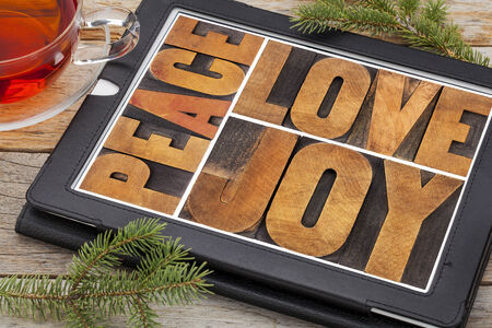 love, joy and peace word abstract on a digital tablet with a cup of tea Stock Photo - 24172110