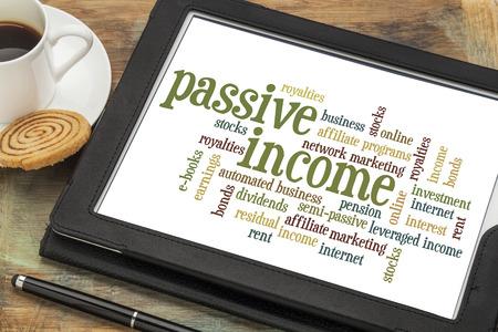 passief inkomen woordwolk op een digitale tablet met een kopje koffie Stockfoto