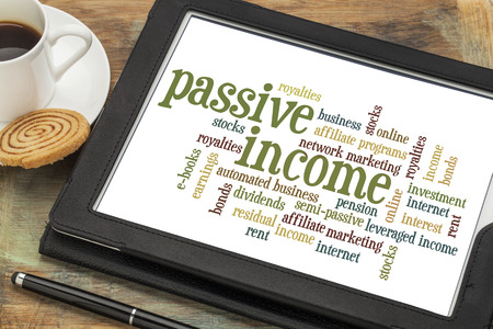 passive: passive income word cloud  on a digital tablet with a cup of coffee