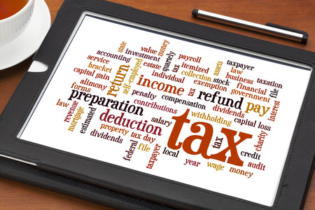 income tax: cloud  of words related to taxes, preparation, paying, income, refunds, on a digital tablet with a cup of tea