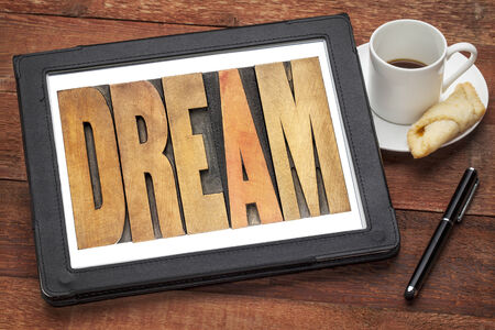dream word in wood type on a digital tablet with a cup of coffee Stock Photo - 24172116