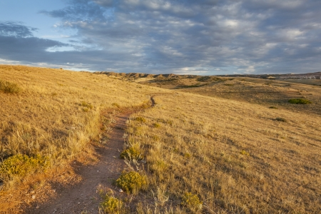 soapstone: sunrise illuminates a trail through rolling grassland at foothills of Rocky Mountains in Colorado - Soapstone Prairie Natural Area near Fort Collins