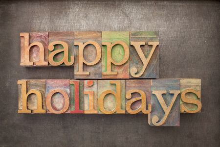 holidays: happy holidays - text in letterpress wood type against grunge metal background