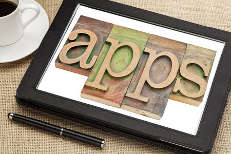 printing block: apps (applications) word in vintage letterpress wood type on a digital tablet with a cup of coffee