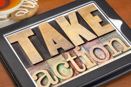 take action - motivation concept -  text in vintage letterpress wood type on a digital tablet Stock Photo - 24258295
