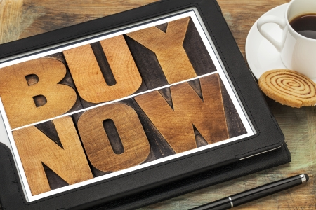 buy now - online shopping concept - word abstract in vintage letterpress wood type on a digital tablet Stock Photo