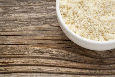 아몬드 가루 단백질 함량이 높고 탄수화물 함량이 적으며 설탕 함량이 낮고 글루텐이 함유되지 않은 제품 - 나뭇결 난 나무 배경에 도자기 그릇