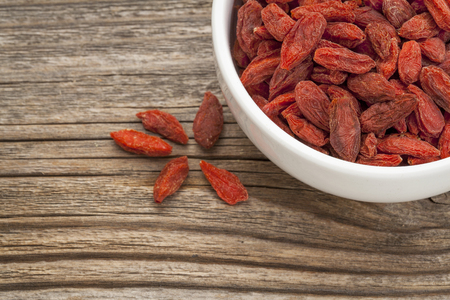 superfruit: goji berries (woldberry) - white ceramic bowl on a grained wood